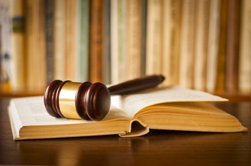 gavel on an open book in front of bookshelf