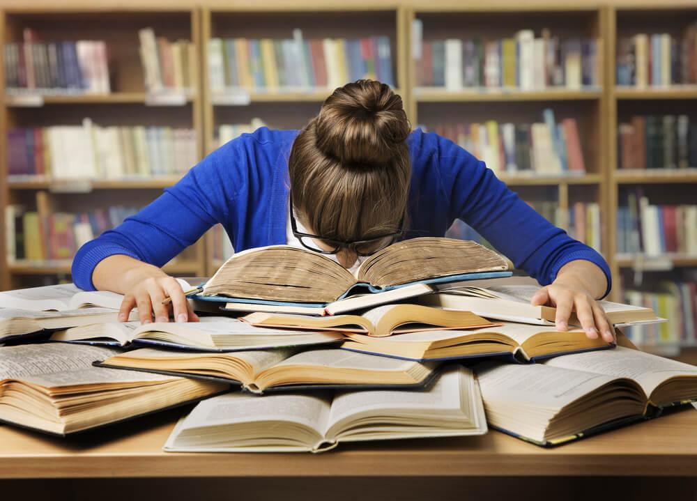 student sleeping on textbooks